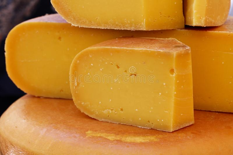 Close up cut slices and wheel of hard gouda cheese royalty free stock photos