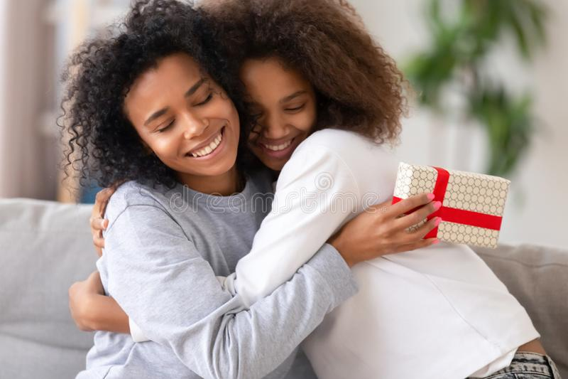 African daughter congratulating mother with birthday relative people embracing royalty free stock photo