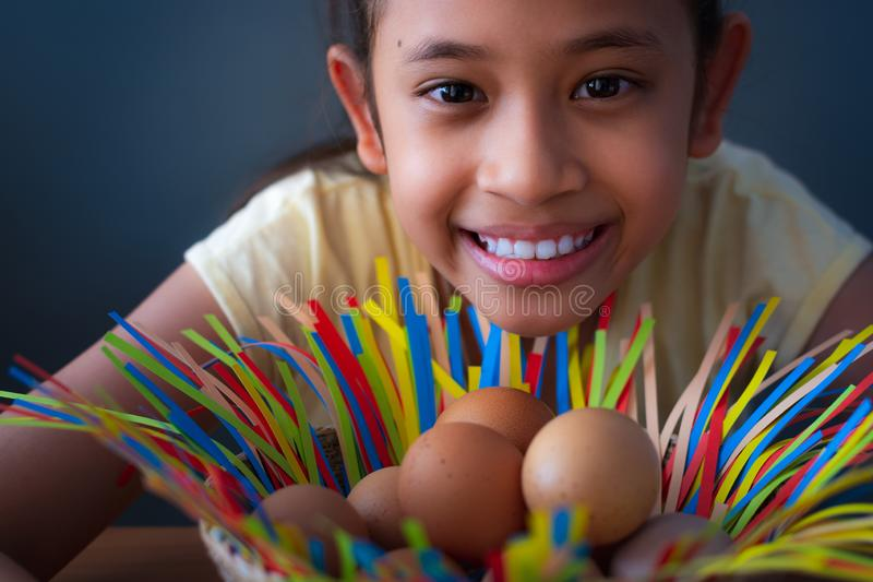 Close up cute asian girl smiling with chicken eggs in a basket stock photography