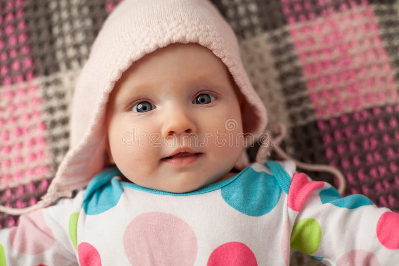 Close up cute baby in a pink hat. Close up cute smiling baby in a pink hat, checkered background royalty free stock image