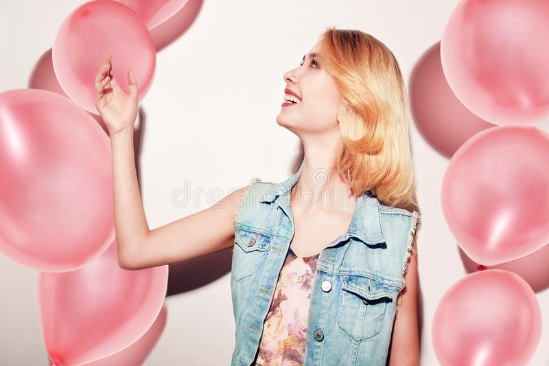 Close-up of cute blonde girl standing in a studio, smiling widely and playing with pink balloons. She wears pink dress, having fun stock photo