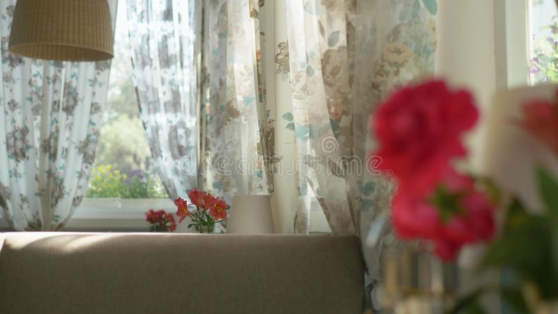 Close-up. A cute bouquet of red roses and freesia in a vase on a table on a sunny summer day in a cafe. transfer of stock images