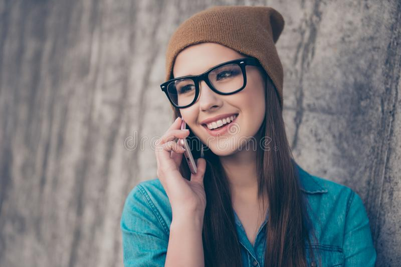 Close up of cute girl, standing near concrete wall outdoors, smiling, talking on her mobile phone. She is wearing casual jeans royalty free stock photography