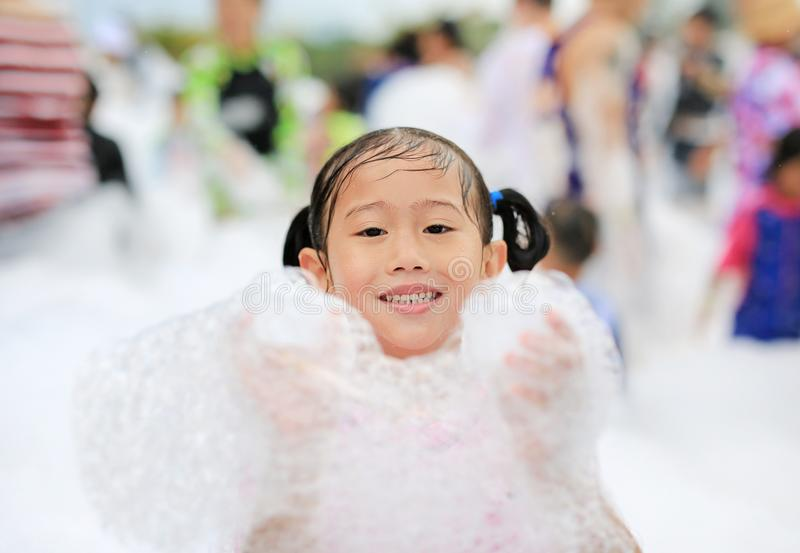 Close-up cute little Asian child girl smiling having fun in Foam Party at the pool outdoor.  stock photography
