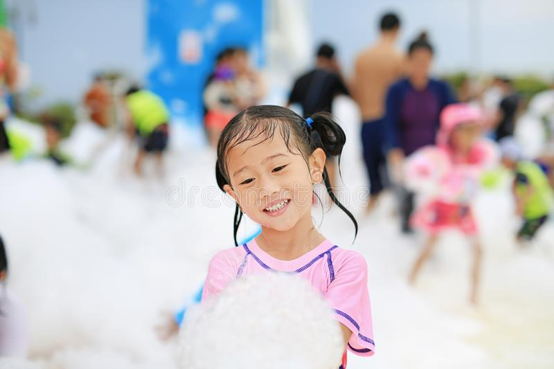 Close-up cute little Asian child girl smiling having fun in Foam Party at the pool outdoor.  royalty free stock photo