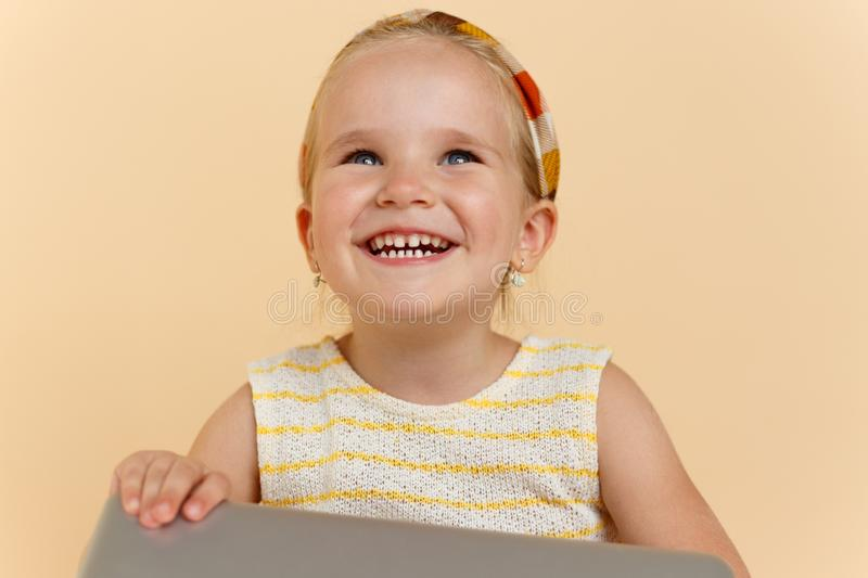 Close up of a cute little girl smiling and looking up, holding a laptope, over beige background. Horizontal view. royalty free stock images