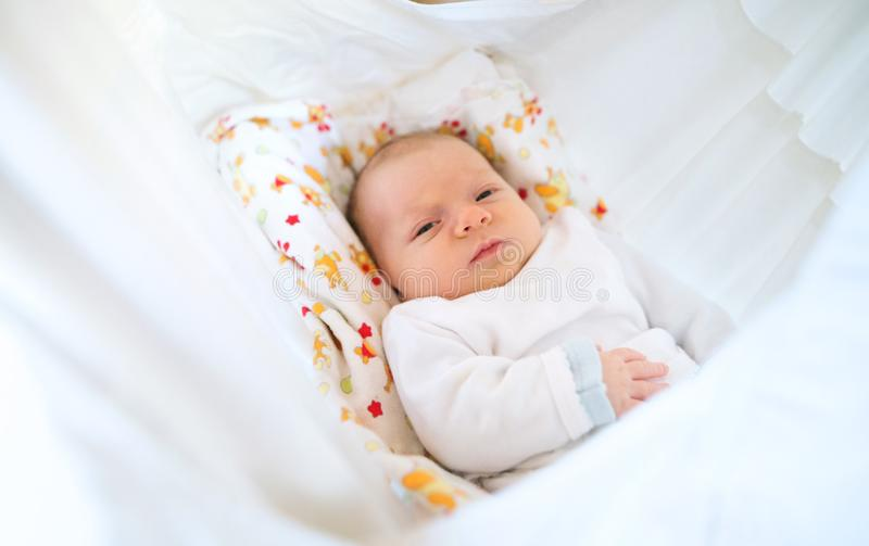 Cute happy newborn baby lying on bed. royalty free stock photos