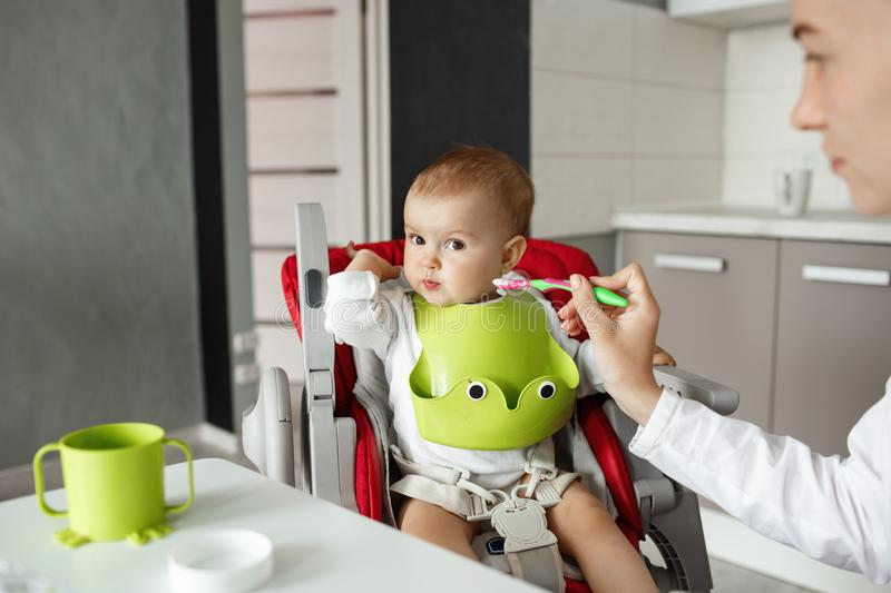 Close up of cute newborn son sitting in kitchen in baby chair and turning head aside refusing to eat baby food. Mother stock image