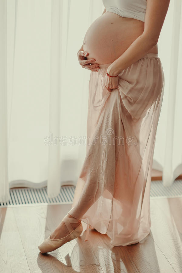 Close up of a cute pregnant belly. Against the window silhouette of a pregnant woman in a pink skirt and pointe royalty free stock photography