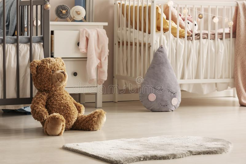 Close-up of a cute teddy bear and a gray raindrop pillow on the floor of a scandi bedroom interior for twins. Real photo stock images