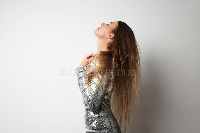 Close-up cute young beatiful woman wearing silver dress and posing at white empty studio background. Copy Space stock image