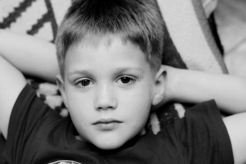 Close up of a cute young boy lying on bed stock photos
