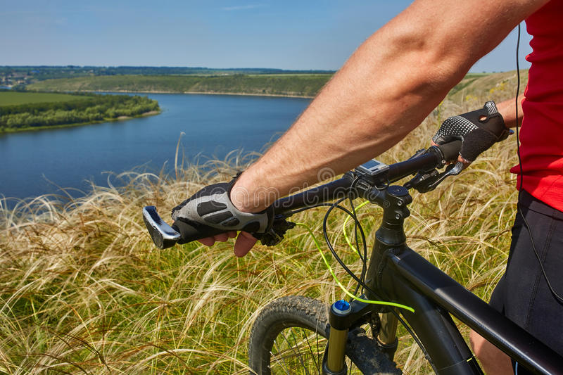 Close-up of the cyclist holding bicycle on the meadow in the countryside against beautiful landscape. stock photo