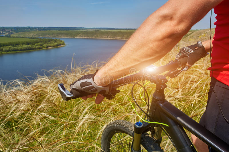 Close-up of the cyclist holding bicycle on the meadow in the countryside against beautiful landscape. royalty free stock images