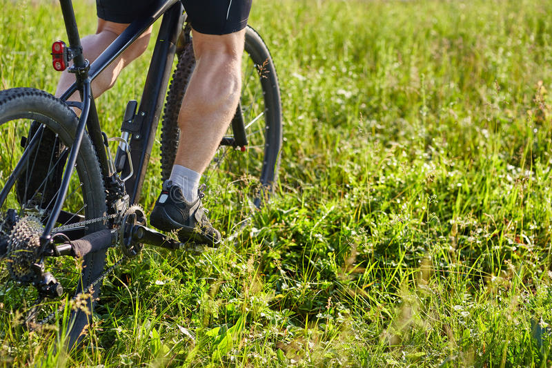 Close-up of cyclist man legs riding mountain bike on the green meadow. royalty free stock image