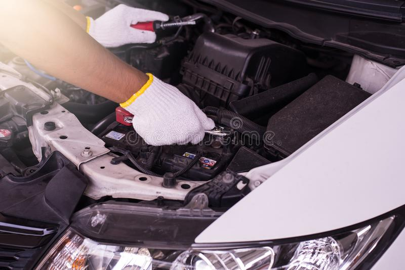 Close up da bateria de carro da fixação do coordenador do mecânico da mão na garagem imagem de stock royalty free