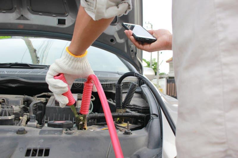 Close-up da bateria e do homem descarregados automóvel de carregamento que chamam ao serviço do mecânico de carro fotografia de stock