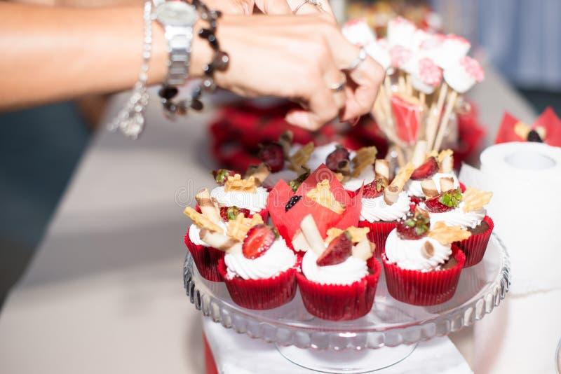 Close up da baunilha caseiro, do bluebery, do limão, dos queques do chocolate e da mão da mulher no fundo de madeira retro branco imagem de stock