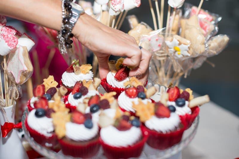 Close up da baunilha caseiro, do bluebery, do limão, dos queques do chocolate e da mão da mulher no fundo de madeira retro branco imagens de stock royalty free