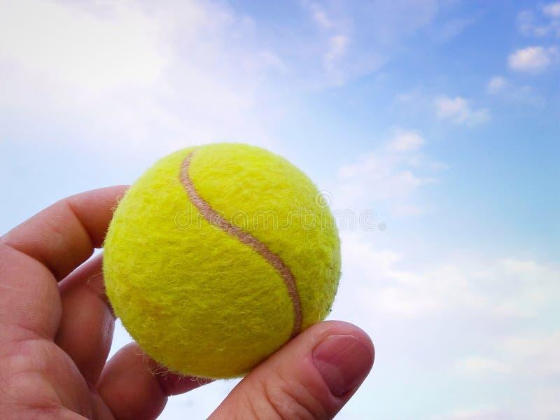Close-up da bola de tênis em um céu azul dos agains da mão do homem imagens de stock