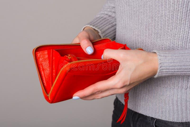 Close-up da bolsa do ` s das mulheres em suas mãos em um fundo cinzento fotografia de stock