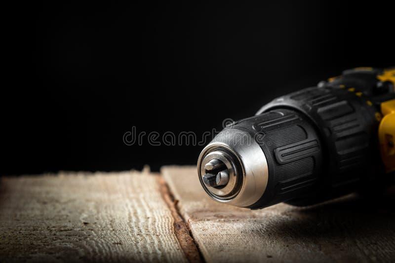 Close up da broca elétrica em um fundo preto com madeira e brocas Ferramentas el?tricas Chave de fenda da bateria da mão foto de stock royalty free