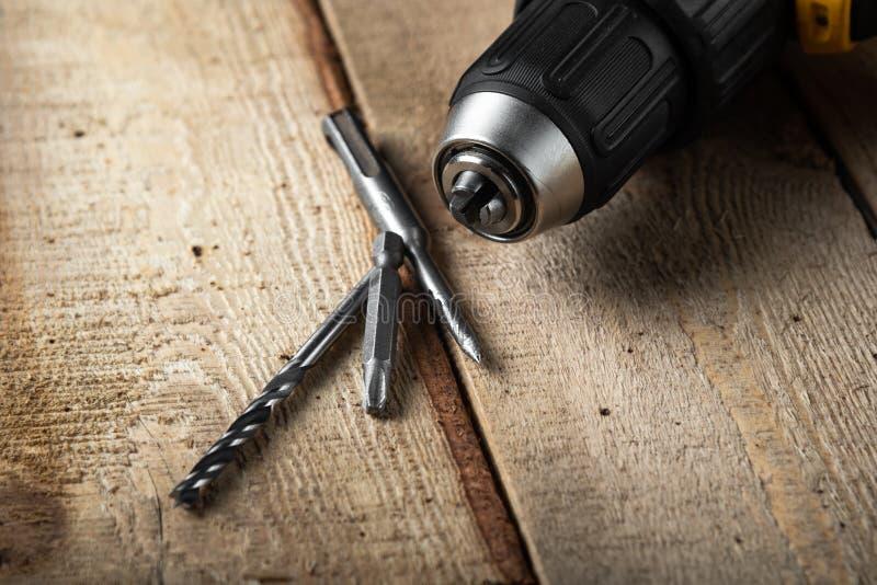 Close up da broca elétrica em um fundo preto com madeira e brocas Ferramentas el?tricas Chave de fenda da bateria da mão imagem de stock