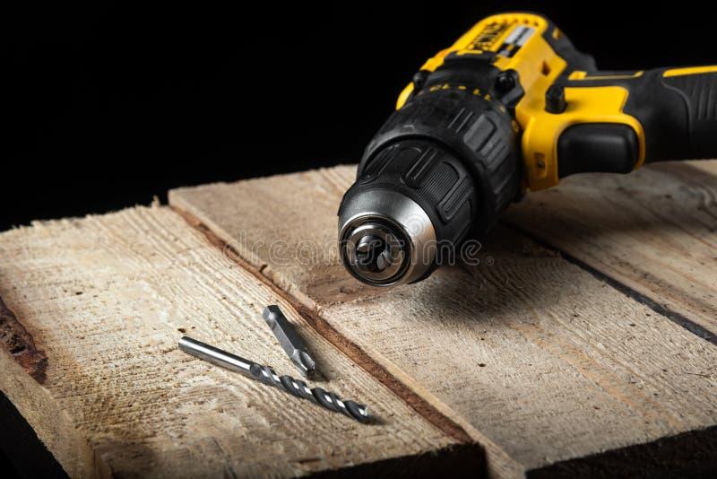 Close up da broca elétrica em um fundo preto com madeira e brocas Ferramentas el?tricas Chave de fenda da bateria da mão fotografia de stock