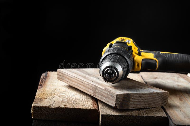 Close up da broca elétrica em um fundo preto com madeira e brocas Ferramentas el?tricas Chave de fenda da bateria da mão fotos de stock royalty free