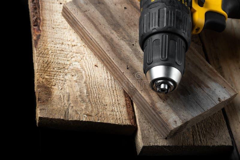 Close up da broca elétrica em um fundo preto com madeira e brocas Ferramentas el?tricas Chave de fenda da bateria da mão fotos de stock