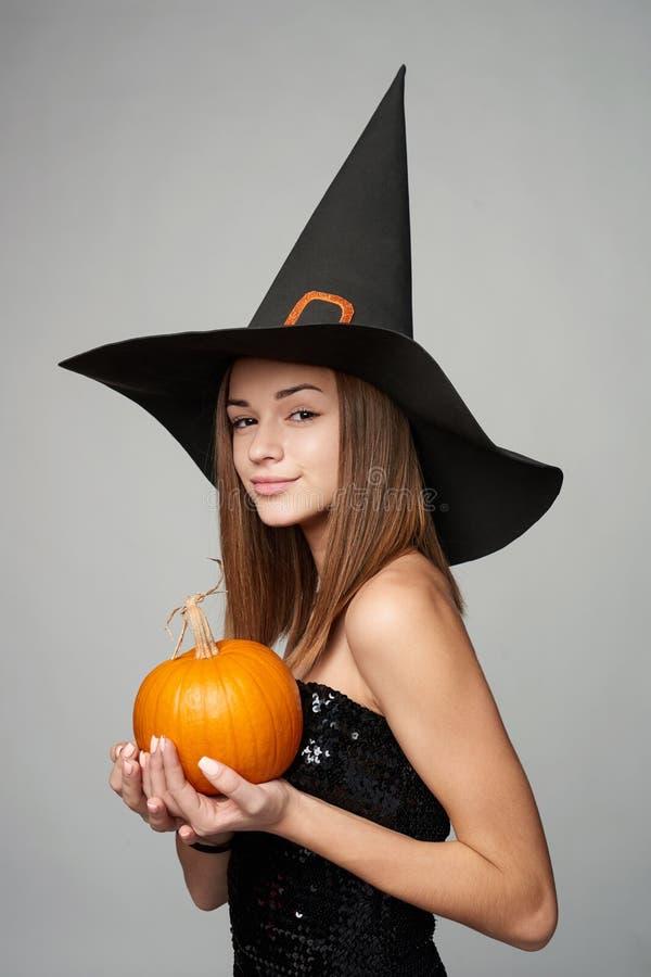 Close up da bruxa brincalhão de Dia das Bruxas que guarda abóboras fotos de stock royalty free