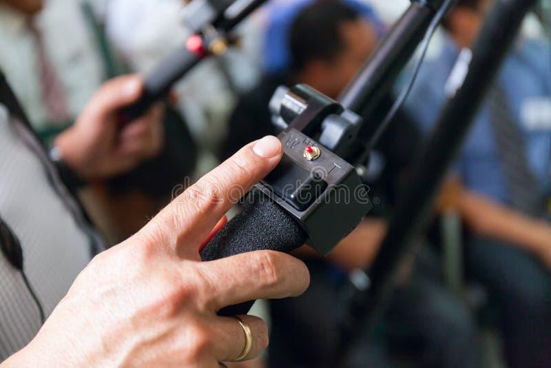 Close-up da câmera de trabalho da mão do homem, operador no trabalho no salão completamente dos povos imagem de stock