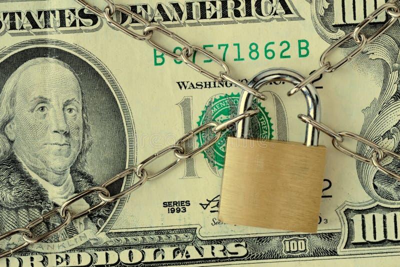 Close up da cédula do dólar travado com corrente e cadeado - conceito do seguro, caução-em e da segurança financeira fotografia de stock