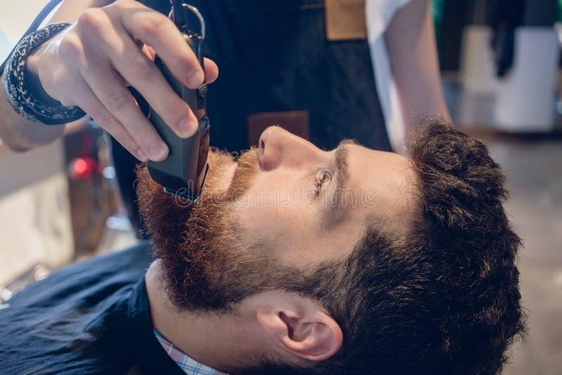 Close-up da cabeça de um homem e da mão de um aparamento do barbeiro foto de stock