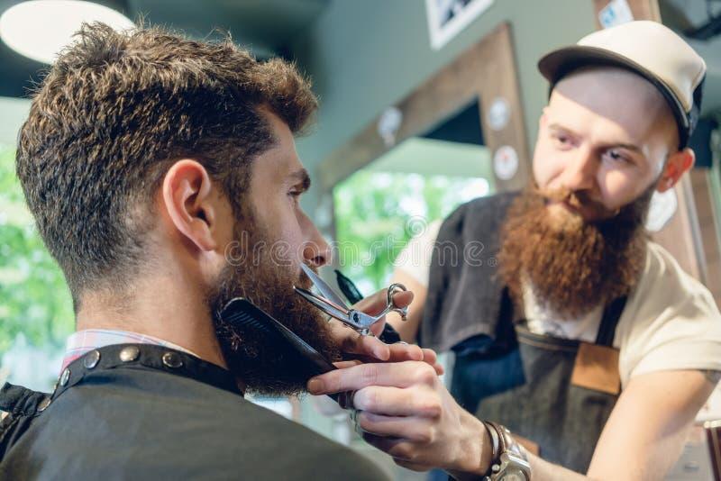 Close-up da cabeça de um homem novo e das mãos de um barbeiro imagens de stock