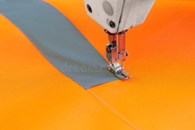 Close up da cabeça da máquina de costura e da tela alaranjada para pro especial imagens de stock
