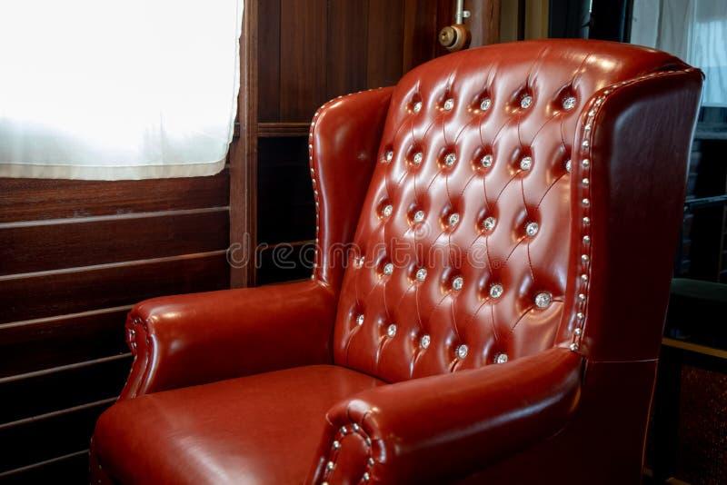Close up da cadeira vermelha de couro do vintage na sala perto da janela foto de stock