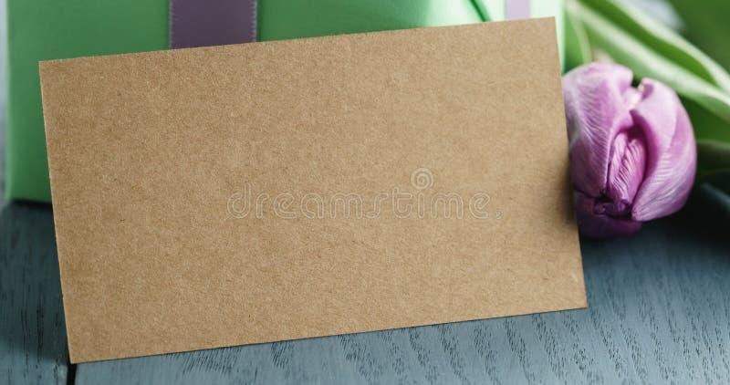 Close up da caixa de presente verde com curva roxa e da tulipa no fundo de madeira azul com cartão vazio imagens de stock royalty free