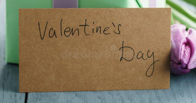 Close up da caixa de presente verde com curva roxa e da tulipa no fundo de madeira azul com o cartão do dia de Valentim fotografia de stock royalty free