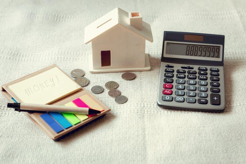 Close-up da calculadora, o dinheiro do dinheiro do dólar, economia de papel da nota e da casa no quarto, operação bancária do neg foto de stock royalty free