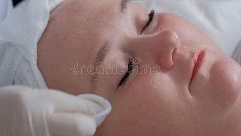 Close-up da cara de uma mulher completa em uma saúde e em um salão de beleza As mãos de um cosmetologist profissional na limpe imagem de stock royalty free