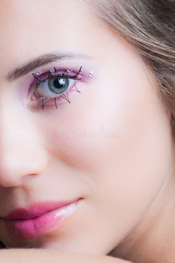 Close up da cara da mulher com as pestanas e os cristais cor-de-rosa da composição imagens de stock royalty free