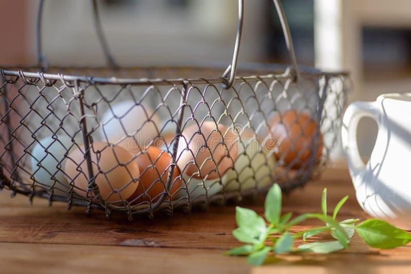 Close up da cesta de fio rústica de ovos frescos na tabela foto de stock