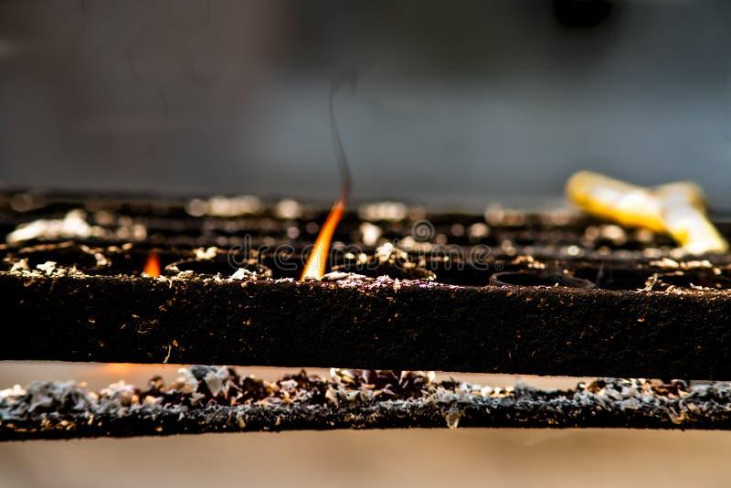 Close-up da chama alaranjada da vela de queimadura no suporte preto do castiçal do metal em um templo budista foto de stock