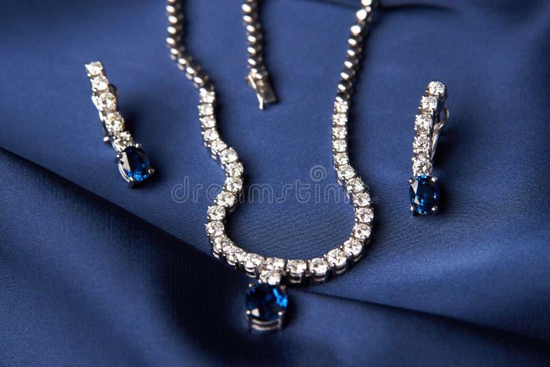 Close-up da colar e dos brincos da platina do ` s das mulheres fotografia de stock