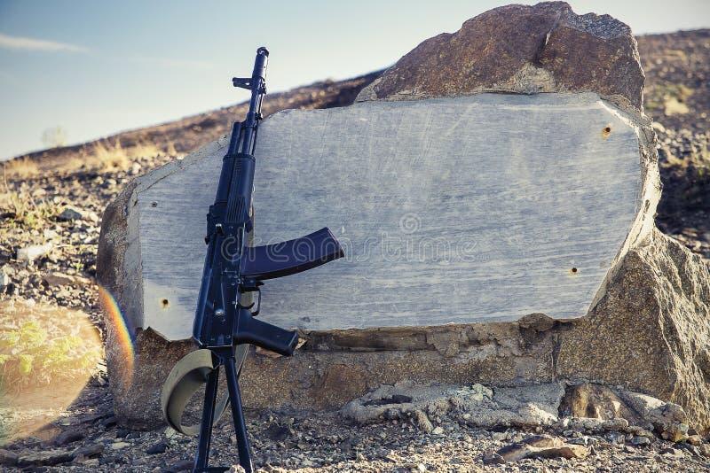 Close-up da espingarda de assalto do Kalashnikov em um fundo de lajes do granito, de monte e do céu azul no fundo fotos de stock royalty free