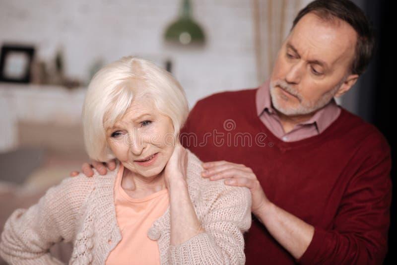Close up da esposa de apoio do homem superior com dor do pescoço fotografia de stock