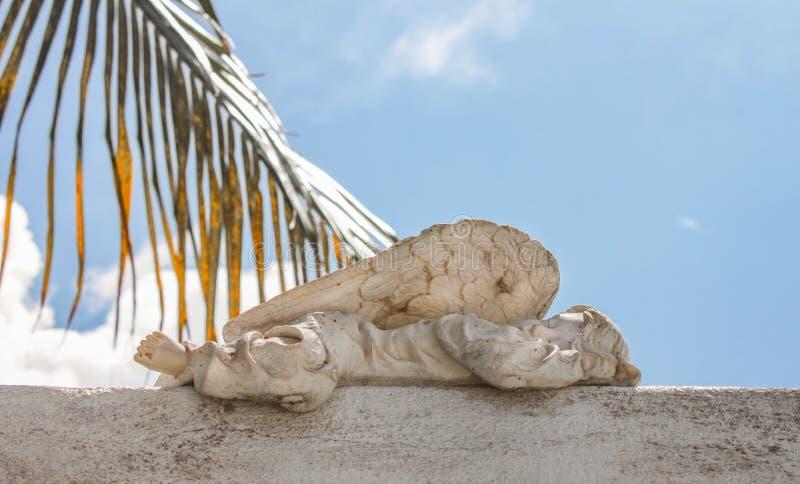 Close up da estátua do anjo do bebê que dorme no cemitério com a fronda azul do céu nebuloso e da palma no fundo foto de stock royalty free