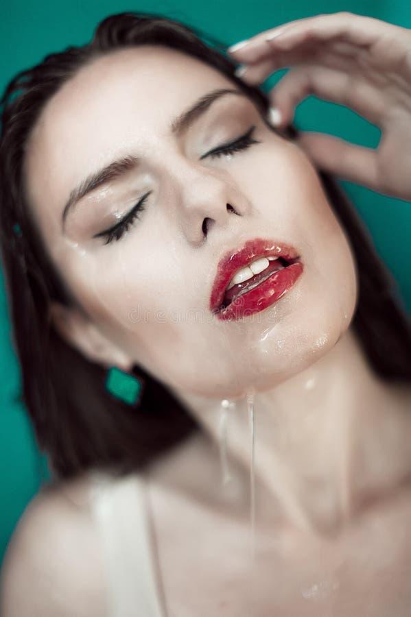 Close-up da face molhada bonita da mulher com gota da água em b verde imagem de stock royalty free