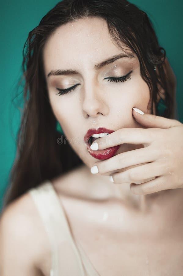 Close-up da face molhada bonita da mulher com gota da água em b verde imagens de stock